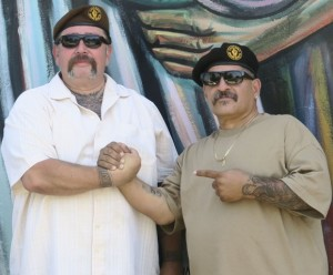 Eliseo Montoya and Mike Castañon, of the Chicano Brown Berets, clasp hands in front of a mural that is adjacent to Ruben Salazar Park in East Los Angeles. Photo by Zamná Ávila